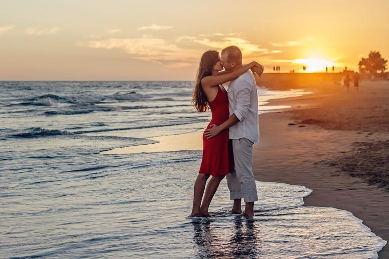 Žena v červených šatách objíma a bozkáva muža v bielej košeli na pláži pri západe slnka.jpg