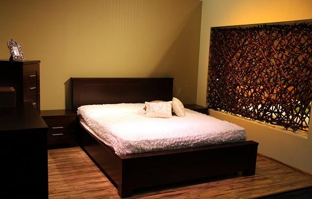 Izba s manželskou posteľou s dreveným čelom, biely matrac a vankúše na posteli.jpg