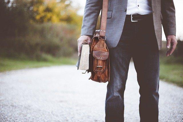 Muž s hnedou taškou a knihou v ruke