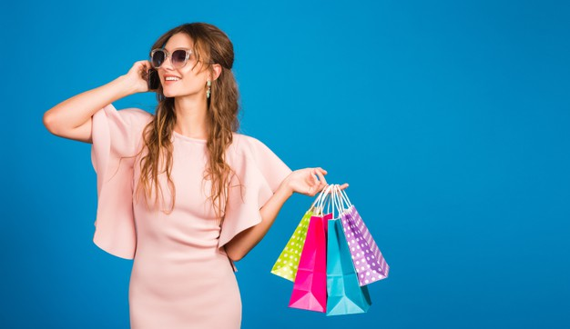 pretty-young-stylish-sexy-woman-pink-luxury-dress-summer-fashion-trend-chic-style-sunglasses-blue-studio-background-shopping-holding-paper-bags-talking-mobile-phone-shopaholic_285396-2957